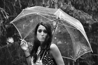 Unhappy woman smoking in the rain